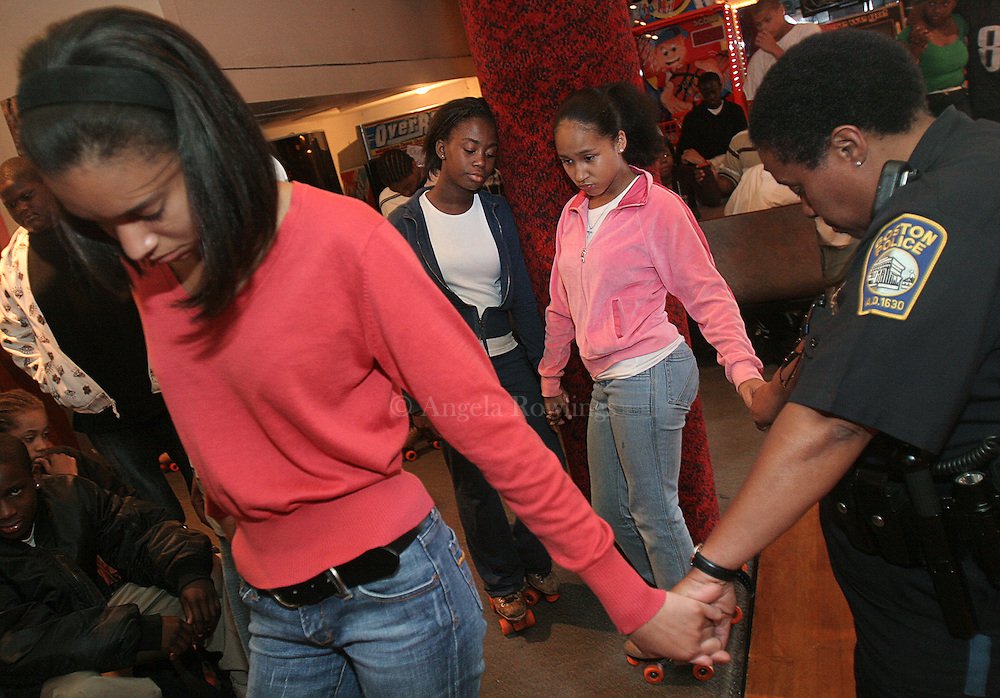 (061307  Boston, MA) Sharnia Dottin, 17, of Cambridge, left, DaLisa Castillo, 10, of Dorchester, Lalani Thistle-Noiles, 13, of Dorchester, and Officer Veritta Pitts hold hands while praying during the Be Smart program at Chez Vous rollerskating rink, Wednesday,  June 13, 2007.    Staff photo by Angela Rowlings.