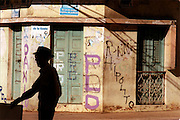 024212.SP.0117.domgame3.kpc--Santa Domingo, Dominican Republic--In the old part of Santa Domingo, a older gentleman walks in the shadows of the buildings mostly homes built 3 and 4 stories high. This middle class area close to the center of the capital city is home to an assortment of age groups.