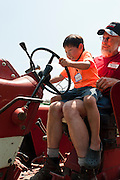 Holden Miller, 5, sits in farmer Steve Querin-Schultz lap and pretends to drive Querin-Schultz's International Harvester tractor during the fourth annual International Student Farm Outing at the Schultz Family Farm in Cottage Grove, Wis., on June 24, 2012. Co-sponsored by the Schultz family and the University of Wisconsin-Madison International Student Services (ISS), the event introduced more than 100 UW-Madison international students and their families, and friends of the Schultz family to agricultural life in rural Wisconsin.