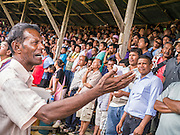 03 NOVEMBER 2012 - HAT YAI, SONGKHLA, THAILAND:  A man looks for people in the crowd to bet with at the bullfighting arena in Hat Yai, Songkhla, Thailand. Bullfighting is a popular past time in southern Thailand. Hat Yai is the center of Thailand's bullfighting culture. In Thai bullfights, two bulls are placed in an arena and they fight, usually by head butting each other until one runs away or time is called. Huge amounts of mony are wagered on Thai bullfights - sometimes as much as 2,000,000 Thai Baht ($65,000 US).      PHOTO BY JACK KURTZ