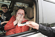 "Snellville resident Kim Jaime reacts after Lilburn Police Sergeant Brian McGann gave her a one-hundred dollar bill from a ""secret Santa"" during a traffic stop on Wednesday in Lilburn. (Staff Photo: David Welker)"