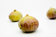 Three Fresh ripe figs on white background