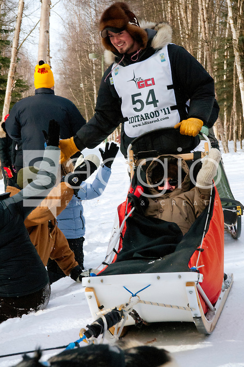 Musher Pete  Kaiser and Iditarider Archie Budzak high-fives as they pass through a crowd of fans along the Chester Creek Trail during the 2011 Iditarod Ceremonial Start.