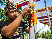 14 JULY 2016 - UBUD, BALI, INDONESIA:  A man works on an alter that will be burned during the mass cremation in Ubud. Local people in Ubud exhumed the remains of family members and burned their remains in a mass cremation ceremony Wednesday. Thursday was spent preparing for Saturday's ceremony that concludes the cremation. Almost 100 people will be cremated and laid to rest in the largest mass cremation in Bali in years this week. Most of the people on Bali are Hindus. Traditional cremations in Bali are very expensive, so communities usually hold one mass cremation approximately every five years. The cremation in Ubud will conclude Saturday, with a large community ceremony.     PHOTO BY JACK KURTZ