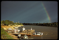 Rainbow arches over Jurua River and barge full of mahogany logs docked at Eirunepe, Amazonas. Brazil