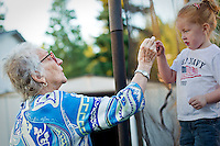 Nancy Coon is handed a pine needle by grandaughter Chloe Hyder  through the net of a trampoline during a family barbecue Sunday, July 25, 2010 in Hayden, Idaho.