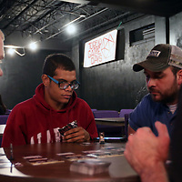 Jamie Nunley, left, Tony Collums, and David Herdahl listen as Game Amassador Josh Harris explains Attack on Titan a deck building card game Saturday at the Tupelo Game Days event at the Link Center