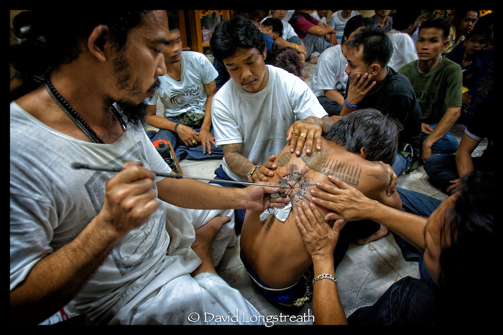 A devotee is tattooed during festivities at the Wat Bangpra Tattoo Festival in  Nakhon Chai Si province on the outskirts of Bangkok, Thailand.
