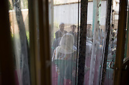 Still with a strict divide between men and women, MP Ms. Fawzia Koofi meets local village men on an outside terrass while the women wait inside the house guarded off by curtains and separate rooms. Faizabad, Badakshan, Afghanistan, 2012