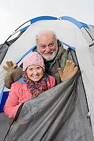 Senior couple in entrance to tent, portrait