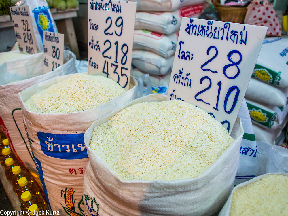"13 FEBRUARY 2014 - BANGKOK, THAILAND: Rice for sale in Khlong Toei Market in Bangkok. The Thai government instituted a ""rice pledging scheme"" after the election in 2011. The government agreed to buy farmers' rice crops at above market prices then planned to warehouse the rice and sell it on international markets when prices recovered. At the same time, India and Vietnam started to export large quantities of rice and the Thai government fell short of funds to pay for rice it had already purchased from farmers. Many farmers have not been paid for rice grown in 2013 and some of the rice in the Thai warehouses is allegedly rotting. Thailand has fallen from number 1 rice exporter in the world to number 3 and several government to government contracts the Thais signed with rice importing countries (like China) have been cancelled. Farmers, once key supporters of the government are now joining anti-government protests in Bangkok and occupying government ministries including the Ministry of Commerce.    PHOTO BY JACK KURTZ"