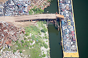 Trucks bring scrap from homes, cars, and other damaged items caused by Hurricane Katrina to a metal yard for recycling. Once items have been crushed and compacted they are placed on barges.