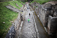 Pompei, Napoli. Turisti in visita agli scavi archeologici di Pompei, percorrono Via di Nola una delle arterie principali dell'antica città romana; Tourists around the ruins of archaeological site of Pompeii.