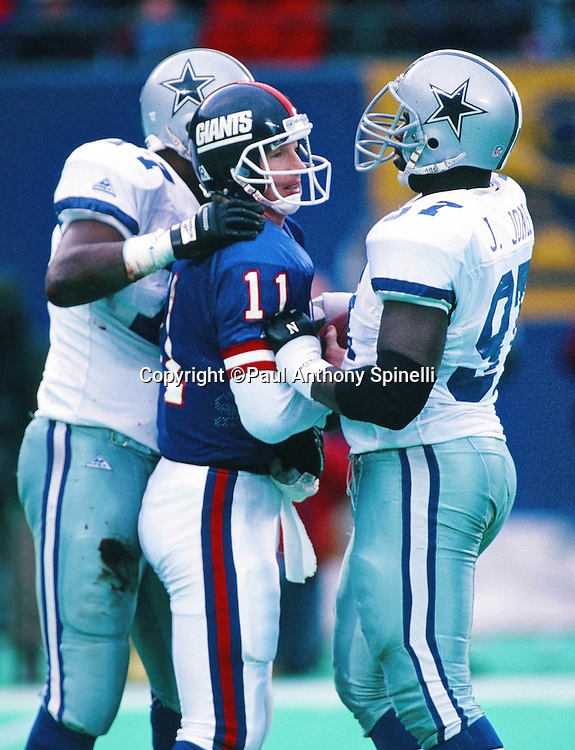 New York Giants quarterback Phil Simms (11) is surrounded by Dallas Cowboys defensive tackle Jimmie Jones (97) and Dallas Cowboys defensive the Jim Jeffcoat (77) during the NFL football game against the Dallas Cowboys on Jan. 2, 1994 in East Rutherford, N.J. The Cowboys won the game in overtime 16-13. (©Paul Anthony Spinelli)