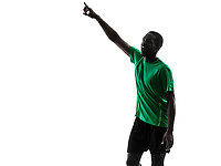 one african man soccer player green jersey pointing in silhouette on white background