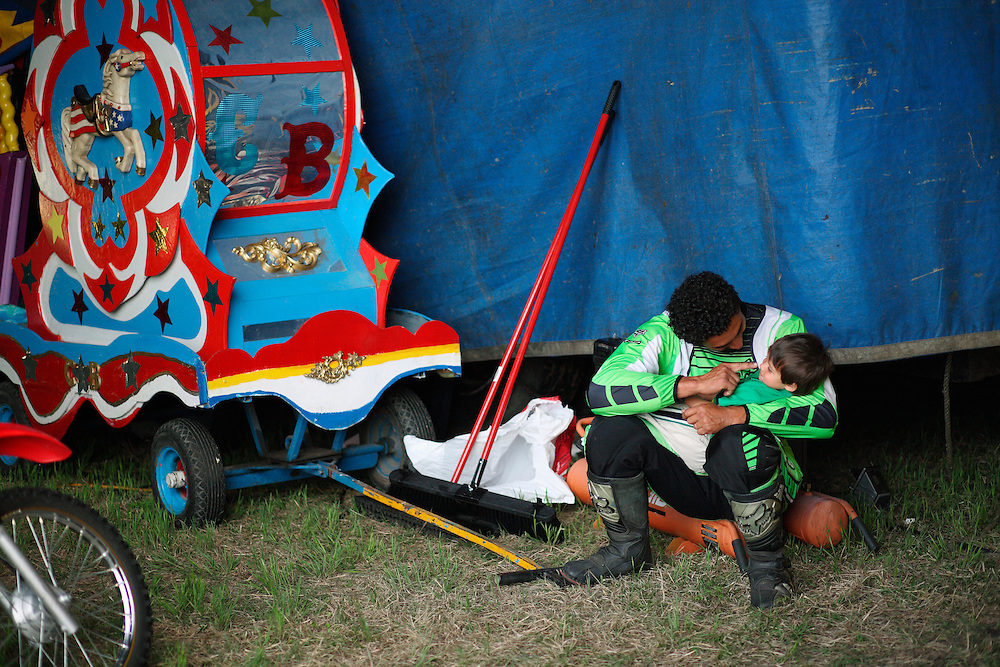 A motorcycle stuntman plays with this son moments before performing at  the Cole Brother Circus