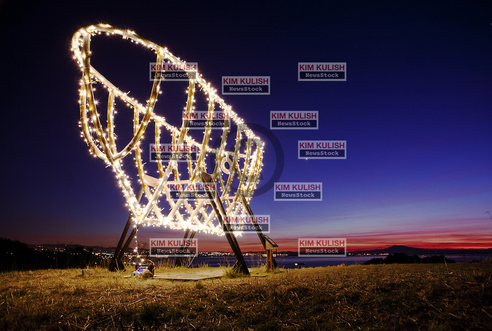 """The """"Ghost Ship"""", adorned with hundreds of LED lights,  glows as the sun sets over the San Francisco Bay December 23, 2011.  The art piece is located high above the southern end of Mare Island in the Shoreline Heritage Preserve."""