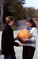 woman holding a large pumpkin handed to her by a handsome man