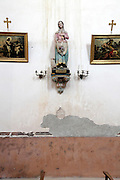 water damaged wall in a church with votive paintings and sculpture