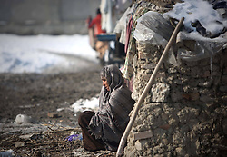 An Afghan refuge elderly woman sits near her tent at a refugee camp in Kabul, Afghanistan, January 2, 2013. Photo by Imago / i-Images...UK ONLY