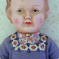 Head and chest of vintage girl doll in central European dress with slightly soiled face and lying on antique paper