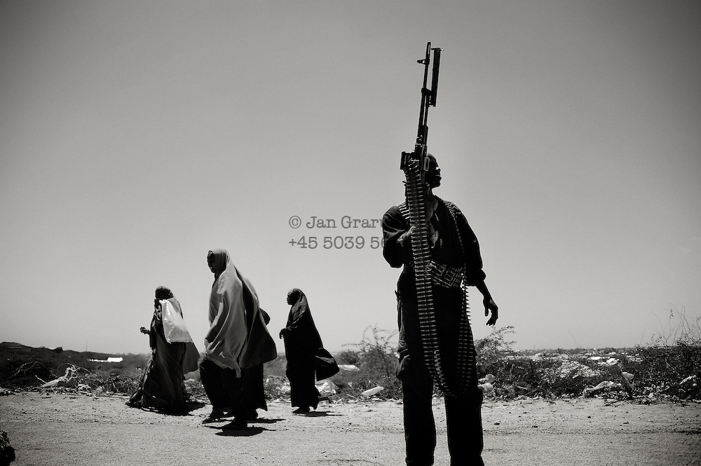 In the Afgoye corridor a guard watches as fefugees arrive from Al- Shabbab territory.