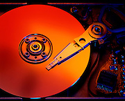 Studio photograph of the interior of a 3.5 inch form factor disk drive with warm sunburst coloration on disk and contrasting blue highlights