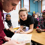 Patrick Whelan '21 of Melrose, Mass., places a visitor sticker on his Bates hoodie while visiting  Mrs. Whitney's sixth grade homeroom class at Martel School on January 16, 2018. Bates students and staff volunteered to share books and read with students as part of MLK day. From left; Hawa Olhaya, Jayden Lord, Jada Cummins, and Fadumo Hussein.