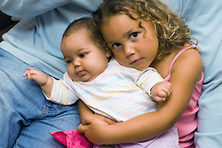 Young girl cuddling her baby sister,