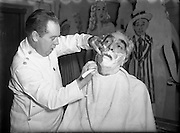 Mr Noel Purcell having his beard removed for Pantomime - Special for Radio Review.23/12/1955