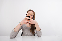 Young businesswoman text messaging on smart phone at office desk