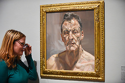 "© Licensed to London News Pictures. 23/10/2019. LONDON, UK. A staff member views ""Reflection (Self-Portrait)"", 1985, by Lucien Freud. Preview of ""Lucian Freud: The Self-portraits"" at the Royal Academy of Arts in Piccadilly.  56 works on display chart Freud's artistic development over almost seven decades on canvas and paper in a show which runs 27 October to 26 January 2020.  Photo credit: Stephen Chung/LNP"