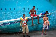 Un grupo de niños posan en un bote durante la festividad del Corpus Christi, representada en Venezuela a traves del ritual magico-religioso de los Diablos Danzantes. Los Diablos de Naiguata se identifican por pintar sus propios trajes y decorarlos con cruces, rayas y circulos, figuras que impiden que el maligno los domine. Las mascaras son en su gran mayoria animales marinos. Llevan escapularios cruzados, crucifijos y cruces de palma bendita. Naiguata, 30 Mayo 2013. (ivan gonzalez)