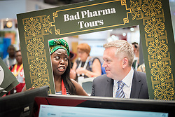 "24 July 2018, Amsterdam, the Netherlands: ""Are you swallowing pharma's lies?"" ask protestors in the Exhibition area of the International AIDS Conference 2018, AIDS 2018, as they visit the Abbott company's exhibition area. The group carry out a ""Bad Pharma Tour"", showcasing pharmaceutical companies' whose humble slogans about good life prospects, say the protestors, do not match up with the way the companies maintain high prices and questionable ethics in order to produce revenue and offer high wages for CEOs and other company representatives."