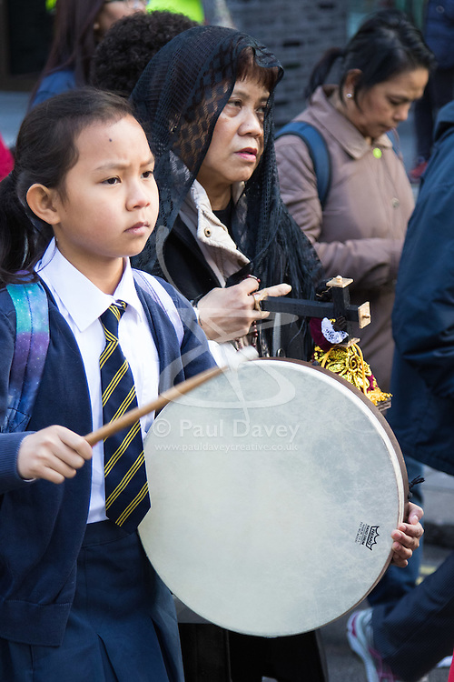 """Westminster, London, March 25th 2016. Westminster's annual interdenominational Easter procession takes place with a procession from Methodist Central Hall to Westminster Cathedral and then on to Westminster Abbey, with the cross borne by people from The Passage, a homeless charity. PICTURED: Her drum beating """"as Jesus' heart"""", a girl from St Vincent de Paul Primary School in Victoria helps to give the procession a solemn air. <br /> ©Paul Davey. <br /> <br /> FOR LICENCING CONTACT: Paul Davey +44 (0) 7966 016 296 paul@pauldaveycreative.co.uk"""