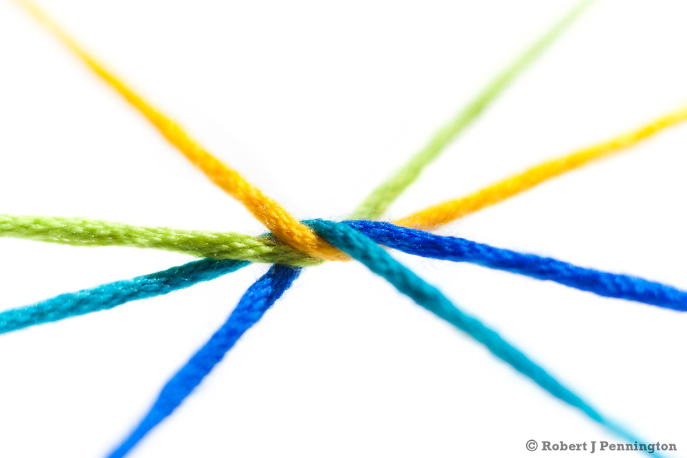 Colored strands of yarn twisted together and held in tension on a white background.