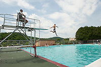 Dylan Sullivan takes a jump off the high dive during the 70th Anniversary celebration of the Kiwanis Pool in St. Johnsbury Vermont.  Karen Bobotas / for Kiwanis International