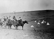 Four Atsina Indians on horseback overlooking tepees in valley beyond, 1908. Photograph by Edward Curtis (1868-1952).