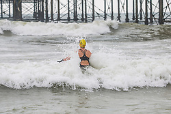 © Licensed to London News Pictures. 24/03/2018. Brighton, UK. Members of the Brighton Swimming Club take part in their daily swim in the sea as milder weather is hitting Brighton and Hove. Photo credit: Hugo Michiels/LNP
