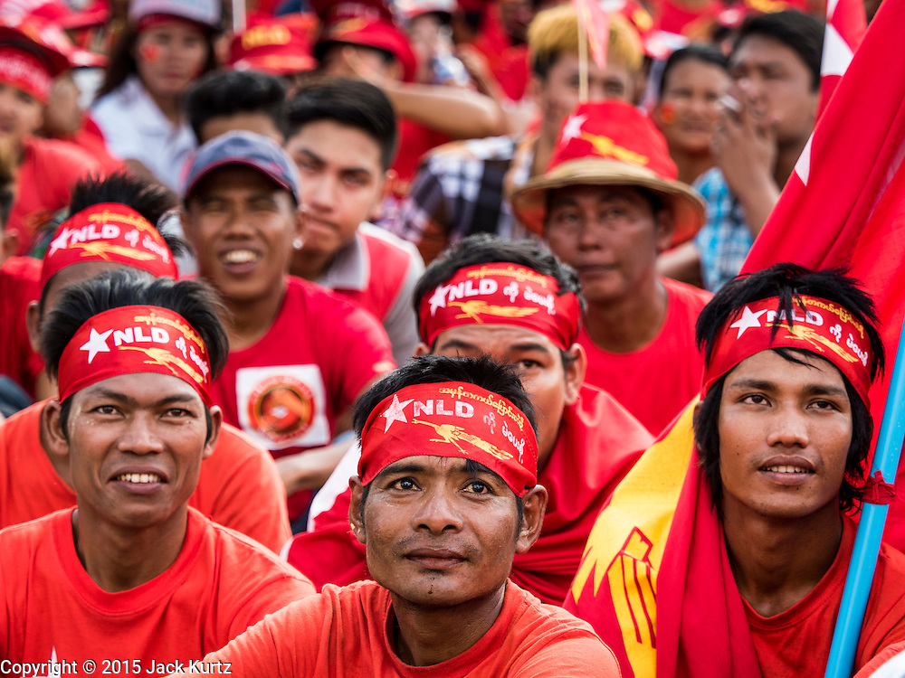 01 NOVEMBER 2015 - YANGON, MYANMAR: Men listen to the entertainment at the NLD's last election rally of the 2015 election in the Yangon suburbs Sunday. Political parties are wrapping up their campaigns in Myanmar (Burma). National elections are scheduled for Sunday Nov. 8. The two principal parties are the National League for Democracy (NLD), the party of democracy icon and Nobel Peace Prize winner Aung San Suu Kyi, and the ruling Union Solidarity and Development Party (USDP), led by incumbent President Thein Sein. There are more than 30 parties campaigning for national and local offices.    PHOTO BY JACK KURTZ