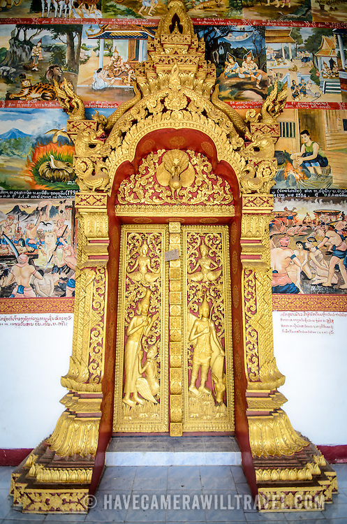 A guilded door surrounded by ornate paintings on the exterior of Wat Phonxay Sanasongkham in Luang Prabang, Laos, near the morning market.
