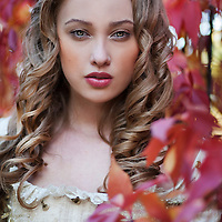 Close up face of elegant young woman with curly hair outdoors alone looking at camera in regency costume