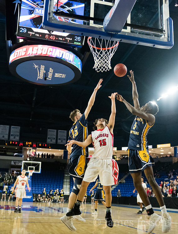 Watertown High School junior Yoseph Hamad goes to the basket while covered by Saint Mary's sophomore Joseph Abate-Walsh (left) and junior Chibuikem Onwuogu during the MIAA Division 3 North sectional final at the Tsongas Center in Lowell, March 10, 2018. Watertown won the game, 44-36.   [Wicked Local Photo/James Jesson]