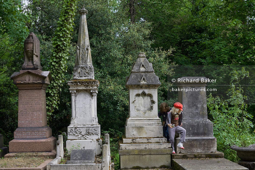 Two young girls play around the grand Victorian memorial grave stones in Nunhead Cemetery whose deceased occupants were important members of society from the industrial age. During this annual open day, it is an opportunity for the Friends of the cemetery to celebrate and educate Londoners, old and young - thereby helping to preserve and conserve this historic site.