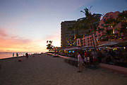 "Sunset at Waikiki Beach. The Mai Tai bar at the historic Royal Hawaiian Hotel, also known as the ""Pink Lady""."
