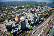Nederland, Amsterdam, Zuideramstel, 12-05-2009; zicht op het financiele centrum van Amsterdam, de Zuidas, met de ringweg A10 en station Zuid/WTC (onder in beeld). Links het hoofdkantoor van ABN-AMRO met daar achter twee torens van het wooncomplex Gershwin. Langs de A10 het complex Mahler 4, in de verte de Vrije Universiteit met academisch zzikenhuis VU en het water van de Nieuwe Meer..Op het tweede plan de wijk Buitenveldert in de achtergrond. Er zijn plannen om snelweg en de spoorlijn te overkluizen of ondertunnelen en dit 'dokmodel' zou door een publiek private samenwerking gerealiseerd moeten worden. Air view on buildings the financial center of Amsterdam, the Zuidas, bottom the ring road A10. In the back the housing district Buitenveldert. .Swart collectie, luchtfoto (toeslag); Swart Collection, aerial photo (additional fee required).foto Siebe Swart / photo Siebe Swart