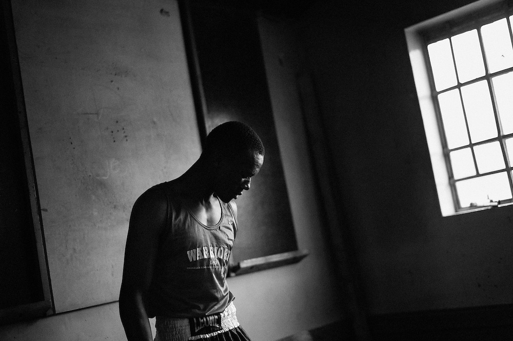 NAIROBI, KENYA - NOVEMBER 17, 2011: Kamau Ng'ang'a prepares mentally for an Olympic Qualifying boxing bout. As a Kikuyu, Ng'ang'a represents the tribe that was targeted most violently during the post-election violence of 2008. Despite his tribal affiliation, Ng'ang'a is the club favorite and hopes to represent the Kibera Olympic Boxing Club in the 2012 Olympics.<br /> <br /> Within Kenya's progressive youth culture is the Kibera Olympic Boxing Club, a group of low-income adolescents from the slum whose leader uses boxing as a way to engage with idle youth. The group's ethnic diversity is remarkable given Kenya's 2008 post-election violence in which people from several tribes were forced violently out of slums. Together, these boxers represent a nascent trend of cross-tribe brotherhood in a healing nation.