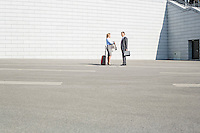 Businesspeople with luggage talking on street