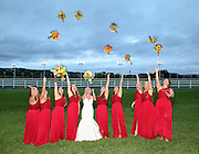 Bride and her bridesmaids throwing their bouquets above their heads at twilight at the Vernon Downs Hotel and Casino, Vernon, NY