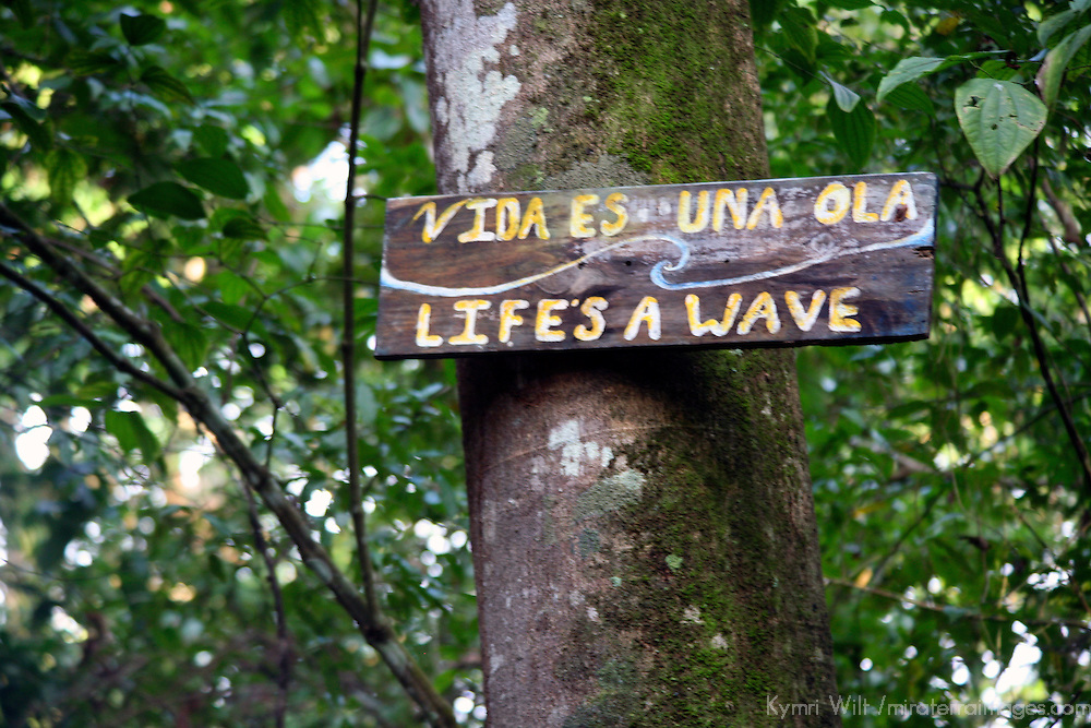 Central America, Costa Rica, Matapalo. Life's A Wave sign on a treeon the path to Matapalo Beach on the Golfo Dulce.